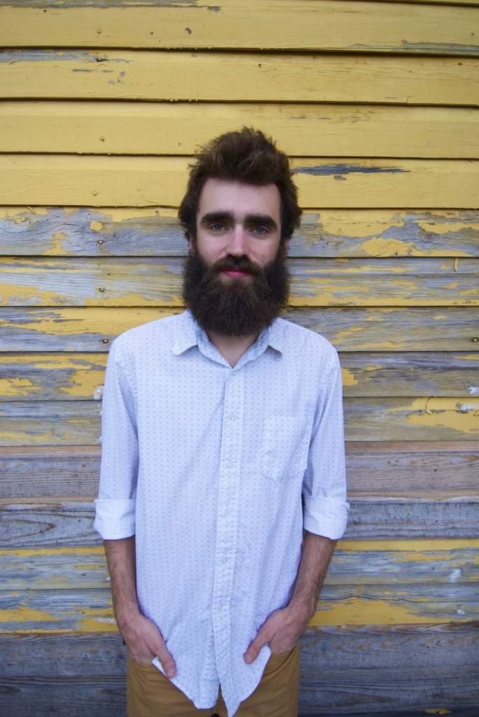 Austin Miller, skinny man with bushy beard, stands in front of weathered wood building. He is artsy. Must be a good musician.